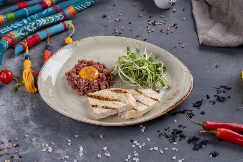 Heerlijke tartare met geroosterd brood en ontsproten tarwe op een plaat Gezonde die lunchmaaltijd van ruw vlees wordt gemaakt kla stock afbeelding