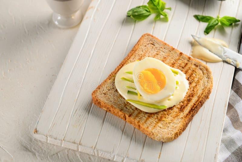 Heerlijke toost met roomkaas en gekookt ei op houten raad royalty-vrije stock afbeeldingen