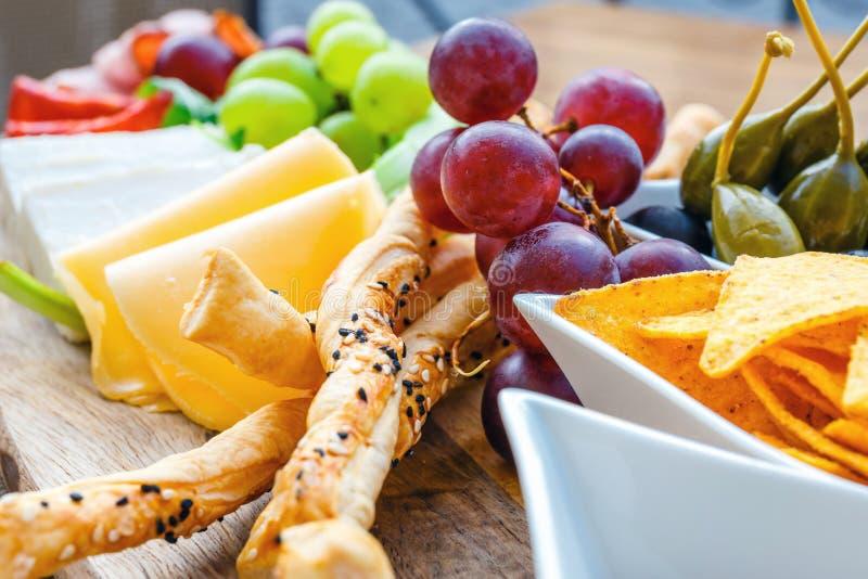 Heerlijke tortillanachos met druiven, pretzels en olijf stock afbeelding