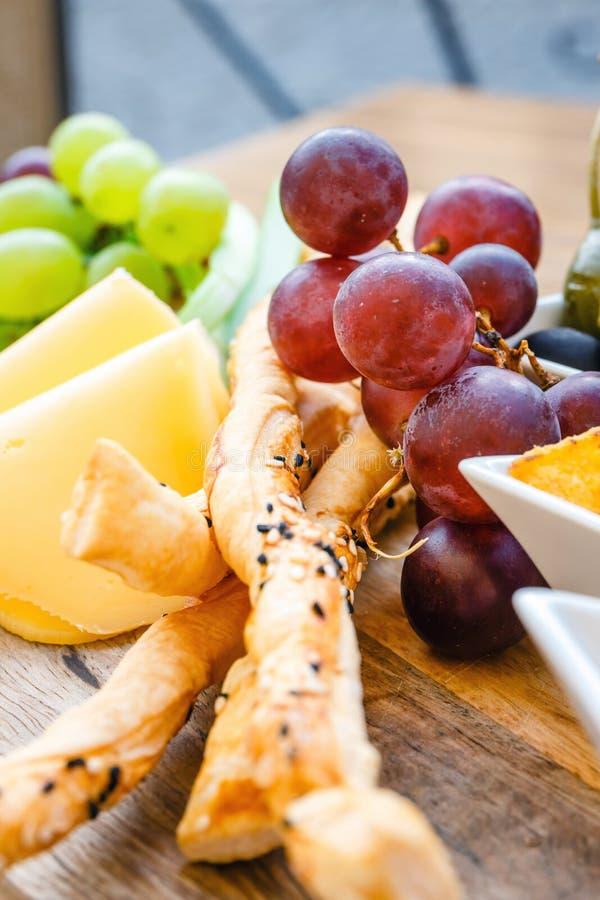 Heerlijke tortillanachos met druiven, pretzels en olijf stock foto
