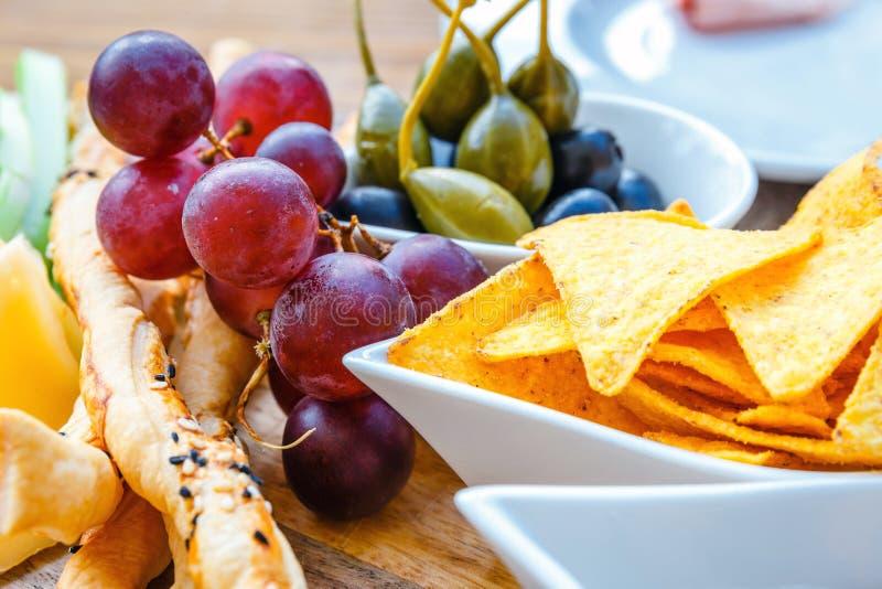 Heerlijke tortillanachos met druiven, pretzels en olijf royalty-vrije stock afbeelding