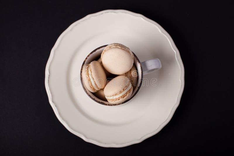 Heerlijke vanille macarons in een witte koffiemok stock foto