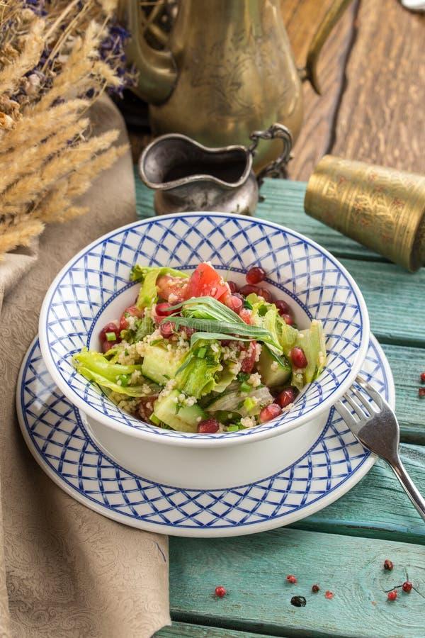 Heerlijke vegetarische quinoa salade met groene paprika, komkommer en tomaten op blauwe houten lijst stock afbeelding