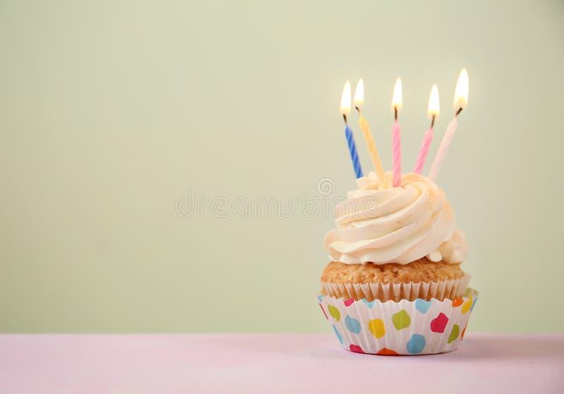 Heerlijke verjaardag cupcake met het branden van kaarsen op kleurentabel stock afbeeldingen