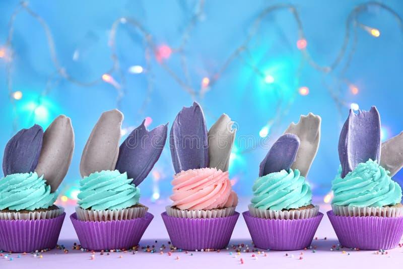 Heerlijke verjaardag cupcakes tegen vage lichten stock foto's