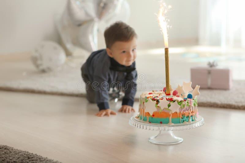 Heerlijke verjaardagscake met vuurwerkkaars voor leuk weinig jongen in ruimte royalty-vrije stock foto's