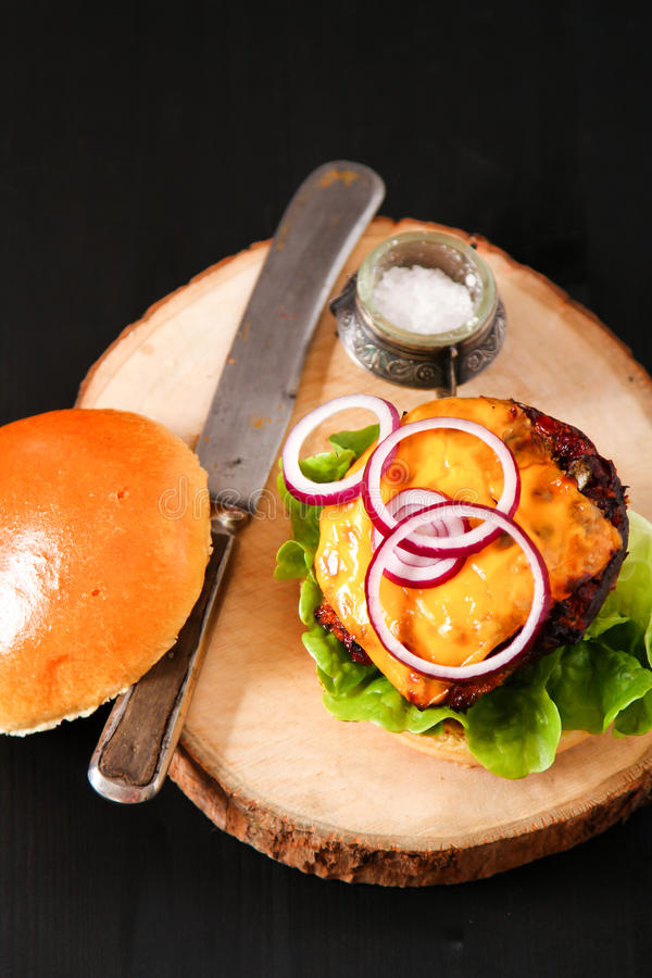 Heerlijke verse eigengemaakte hamburger op donkere dienende raad met kruidig stock afbeelding