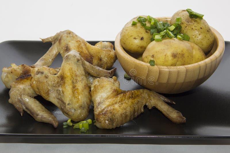 Heerlijke vleugels en aardappel stock fotografie