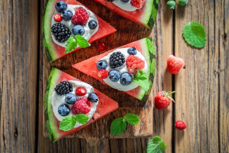 Heerlijke watermeloenpizza met slagroom en verse bessen stock foto