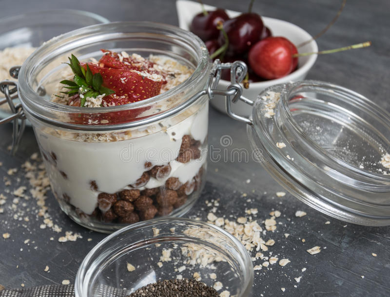 Heerlijke witte yoghurt in een glas met chocoladeballen, havermeel en fruit stock fotografie