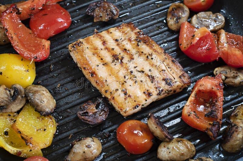 Heerlijke zalm en groenten op de grill Close-up bij het roosteren van vierkante vormzalm, rode en gele peper, kersentomaten stock fotografie