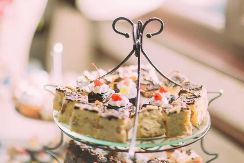 Heerlijke zoete cakes op de huwelijkslijst stock foto's