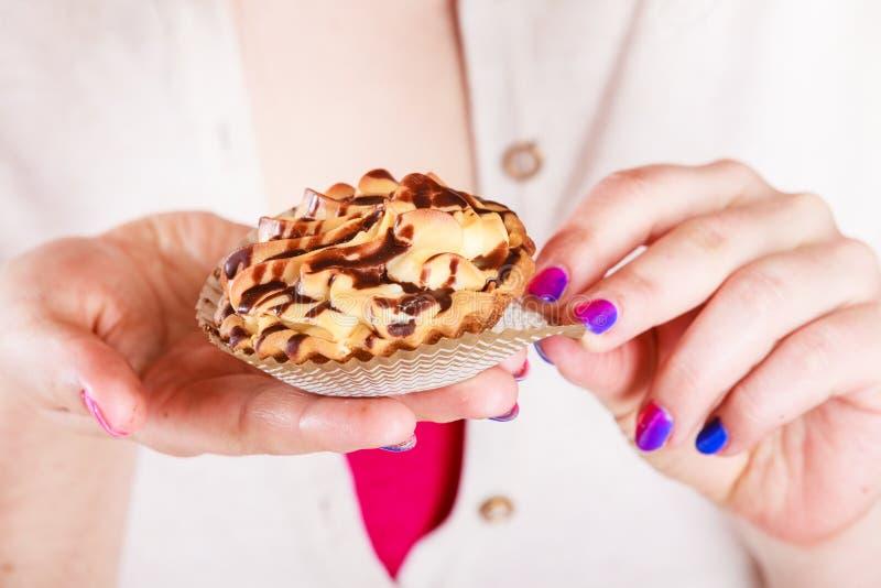 Heerlijke zoete cupcake in menselijke handen gluttony royalty-vrije stock foto