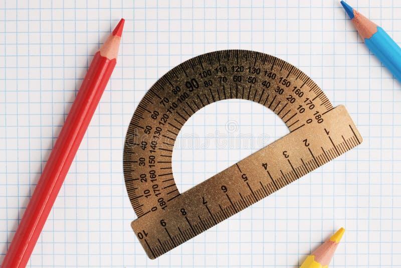 Heersersgradenboog en potloden op een notitieboekjeblad stock fotografie