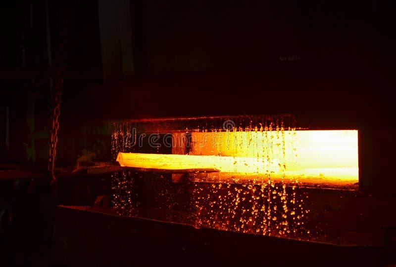 Heet die ijzer in smeltery door een arbeider wordt gehouden Het smelten van metaal in een staalfabriek stock foto's