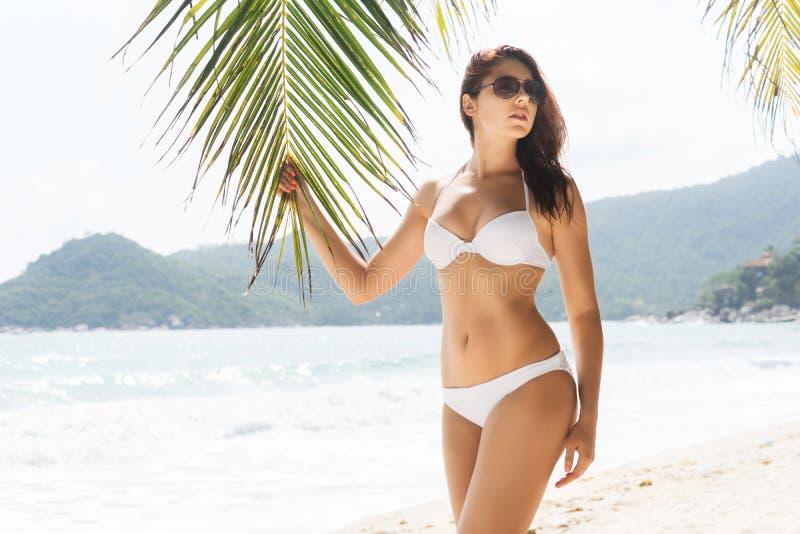 Heet en mooi meisje die zonnebril en verleidelijke witte swimwear dragen stock foto's