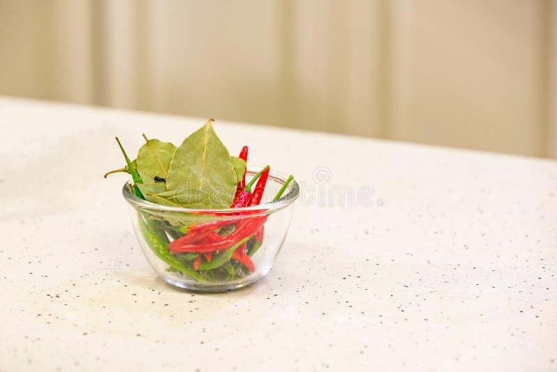 Heet rood en groene paprika's met kruiden in een kom voor Smakelijke Spaanse pepersaus in kom op keukenachtergrond royalty-vrije stock fotografie