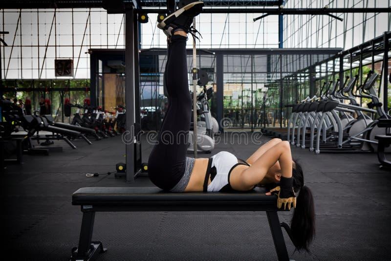 Heft het sportieve vrouwen mooie lichaam die benen doen op bank in geschiktheidsruimte op royalty-vrije stock afbeelding