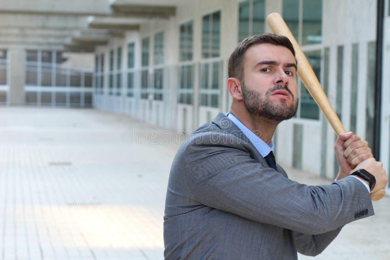 Heftiger schauender Mann, der Baseballschläger hält stockbild
