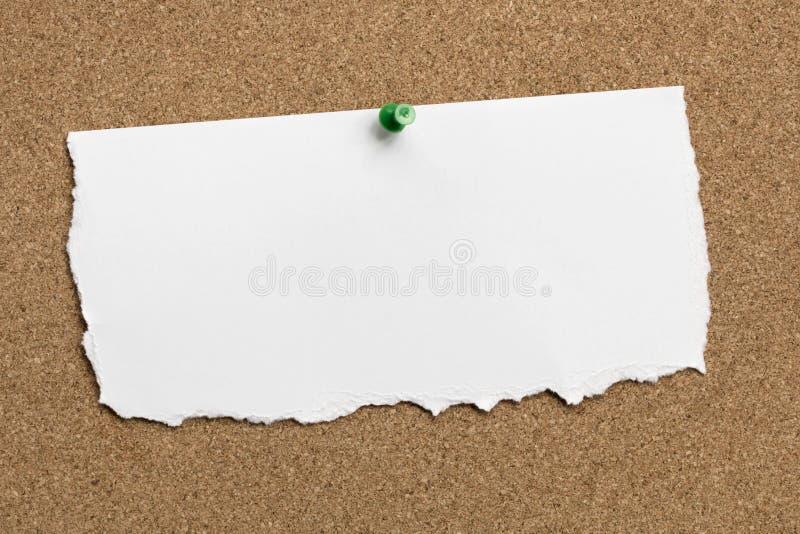 Heftiges Weißbuch mit grünem Reißnagel Pin auf Cork Board stockfotos