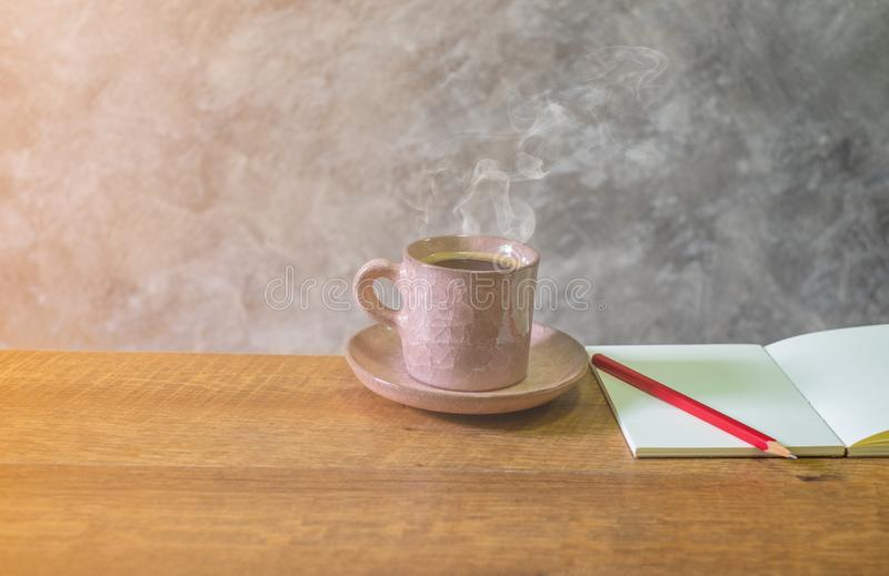 Heiß ein rosa Pastellaltes des Schalenkaffees, das wohlriechendes Aroma mit leerem offenem Buch hat, roter Bleistift auf Holztisc lizenzfreie stockbilder