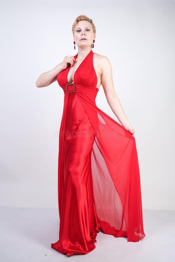 Heiße blonde kaukasische Frau, die langes rotes Glättungskleid und Aufstellung auf weißem Studiohintergrund allein trägt modernes lizenzfreie stockfotos