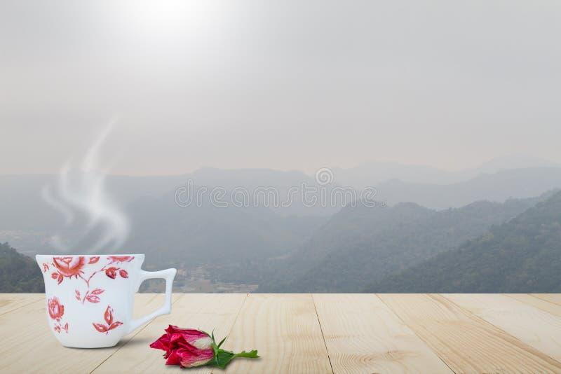 Heiße Kaffeetasse mit Dampf und roter Blume auf die Weinleseholztischoberseite auf unscharfem nebeligem Gebirgshintergrund stockfotografie