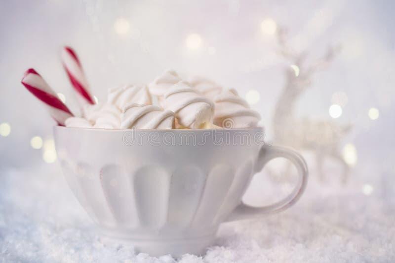 Heiße Kaffeetasse mit Eibischen und roter Zuckerstange auf einem eisigen Winterhintergrund Weihnachtsfeiertagshintergrund stockfotografie
