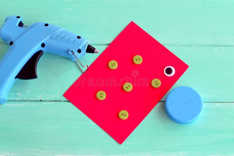 Heiße Klebergewehr Eine Kappe von einer Plastikflasche, Knöpfe, Pappblatt, ein Plastikauge - stellen Sie für die Herstellung des  lizenzfreies stockfoto