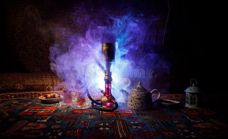 Heiße Kohlen der Huka auf shisha Schüssel, die Dampfwolken am arabischen Innenraum macht Orientalische Verzierung auf der Teppich stockbilder