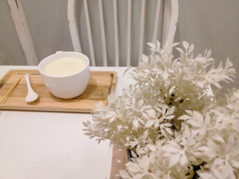 Heiße Milch in der weißen Schale im auf dem Tisch, Weiß, verziert mit Bäumen und Weiß lizenzfreies stockbild