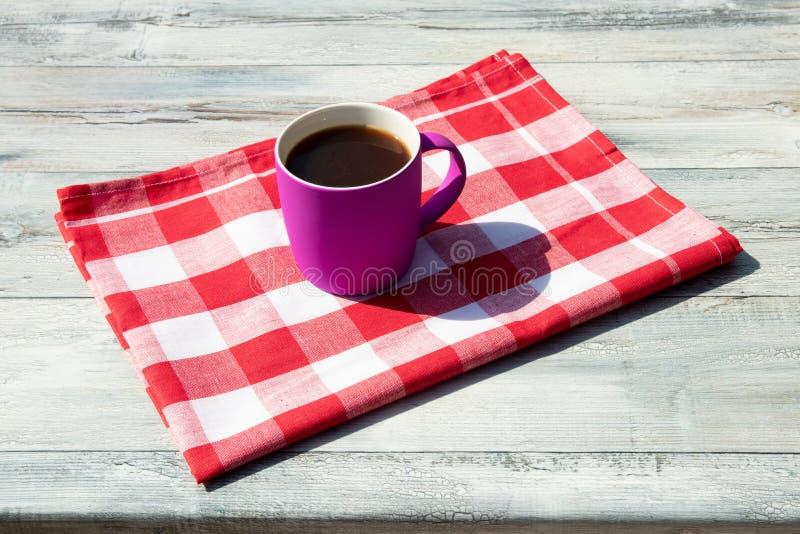 Heiße purpurrote Schale schwarzer Kaffee auf roter weißer karierter Tischdecke lizenzfreies stockfoto
