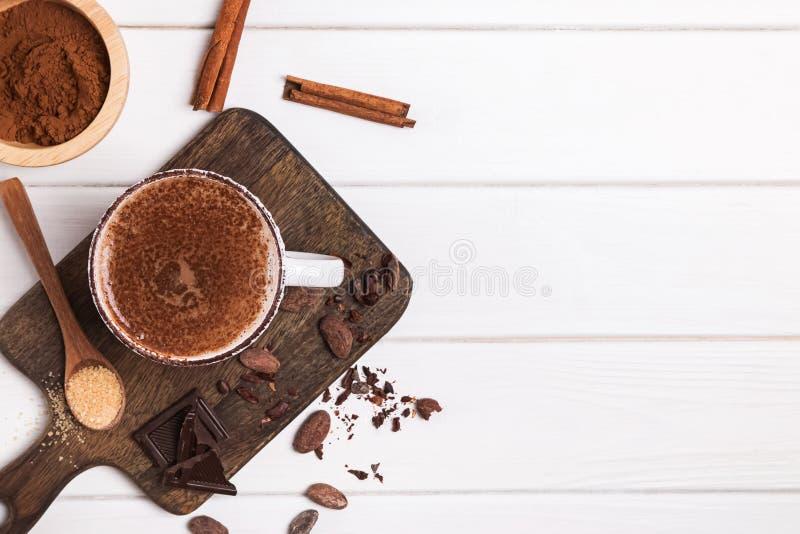 Heiße Schokolade in der Schale, in den Kakaobohnen und im Pulver auf dem weißen Holztisch stockfotografie