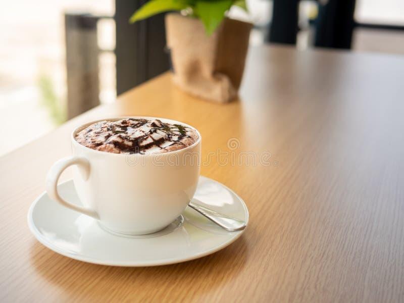 Heiße Schokolade in einer weißen Schale, auf hölzerner Tabelle stockbild