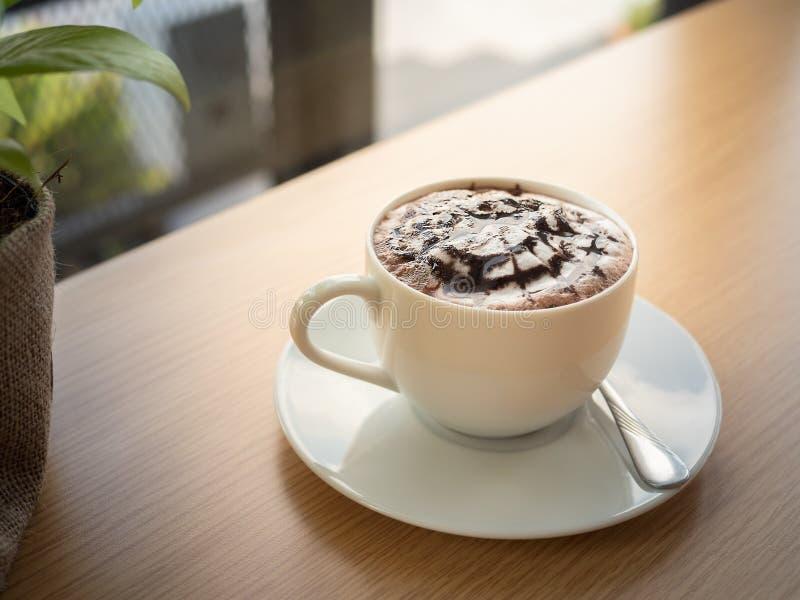 Heiße Schokolade in einer weißen Schale, auf hölzerner Tabelle stockfotografie