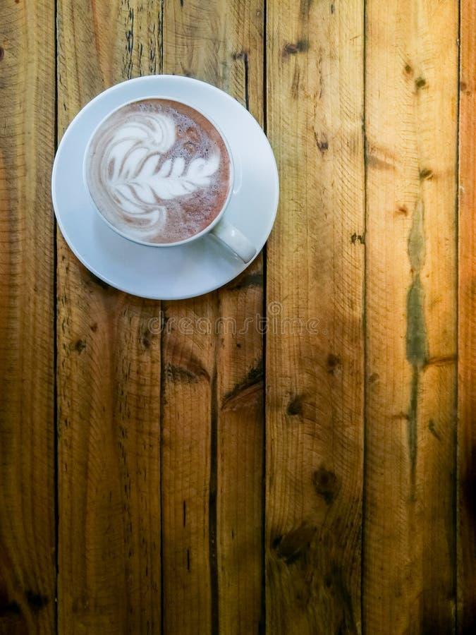 Heiße Schokolade in einer weißen Schale, auf hölzerner Tabelle, Handversuch, zum von a auszuwählen lizenzfreies stockbild