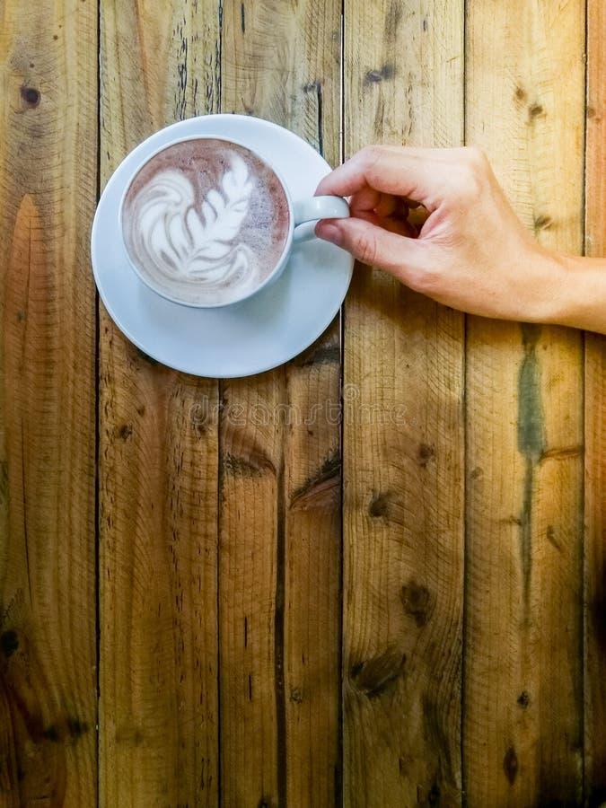 Heiße Schokolade in einer weißen Schale, auf hölzerner Tabelle, Handversuch, zum von a auszuwählen stockfotos