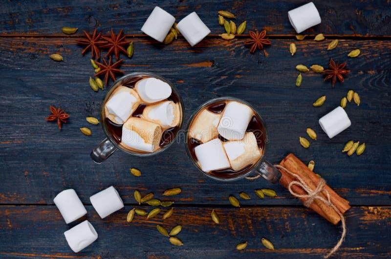 Heiße Schokolade mit den Eibischen verziert mit Wintergewürzen - Zimt, Kardamom und Anis auf dem schwarzen hölzernen Hintergrund lizenzfreie stockfotografie