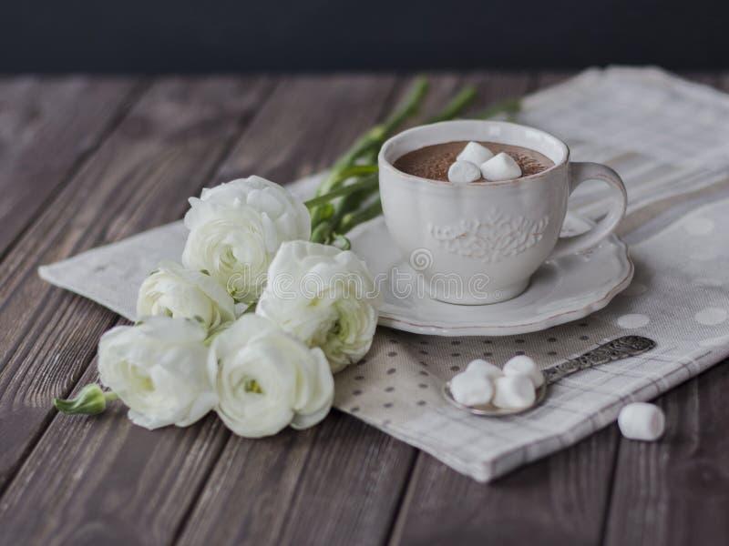 Heiße Schokolade mit Eibisch- und Butterblumeblumenstrauß in der dunklen Tabelle stockfoto