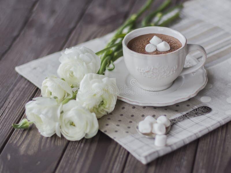 Heiße Schokolade mit Eibisch- und Butterblumeblumenstrauß in der dunklen Tabelle stockbilder