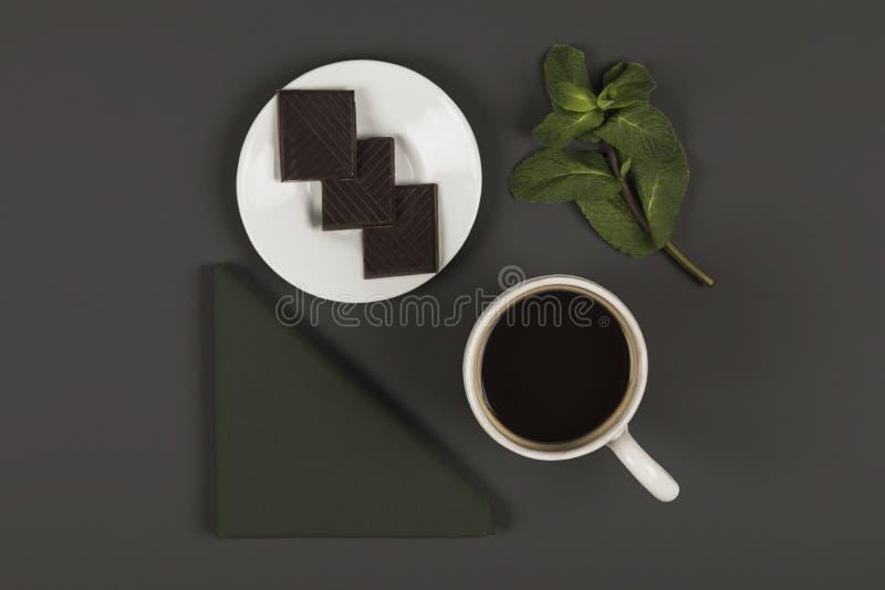 Heiße Schokolade mit tadellosen Blättern der Serviette u. Schokoladenquadraten stockbild