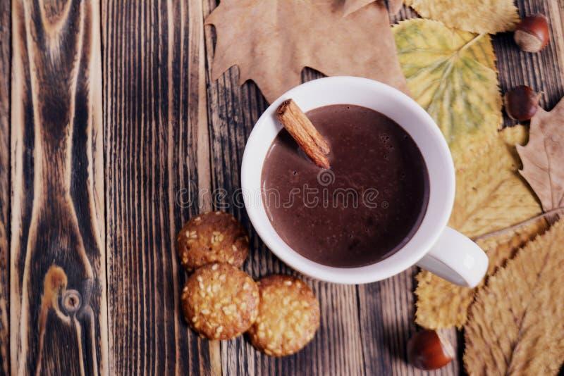 Heiße Schokolade mit Zimtstange in der Schale verlässt Nüsse, die Plätzchen Orangen auf Holztisch trockneten lizenzfreie stockfotografie