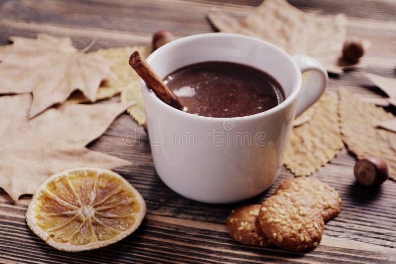 Heiße Schokolade mit Zimtstange in der Schale verlässt Nüsse, die Plätzchen Orangen auf Holztisch trockneten lizenzfreie stockfotos
