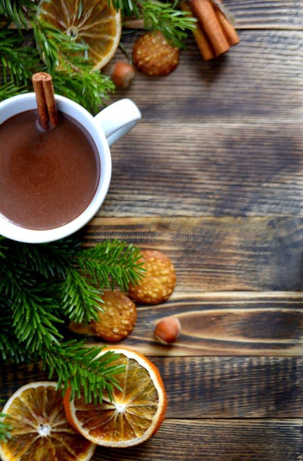 Heiße Schokolade oder Kakao mit Zimtstange in einer Schale und in den Tannenzweigen lizenzfreies stockbild