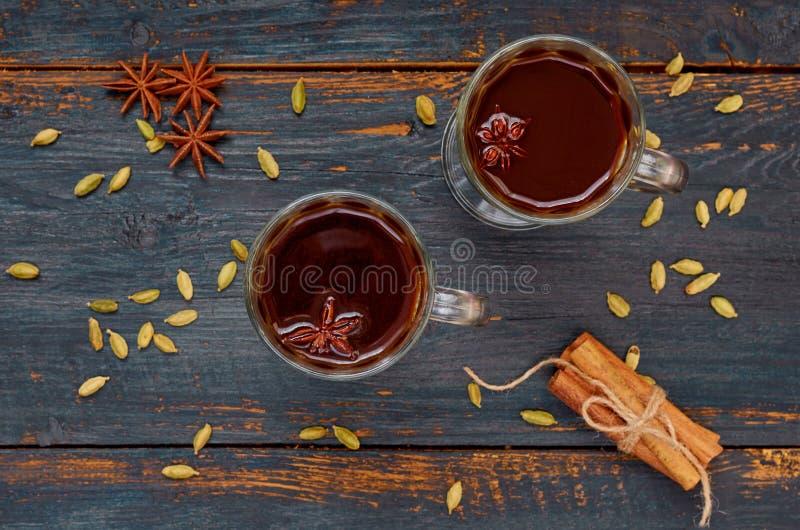 Heiße Schokolade verziert mit Wintergewürzen - Zimt und Kardamom auf dem schwarzen hölzernen Hintergrund stockfoto