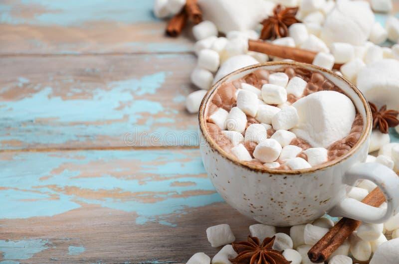 Heiße Schokolade, weiße Eibische und Winter-Gewürze auf blauem hölzernem Hintergrund stockbild