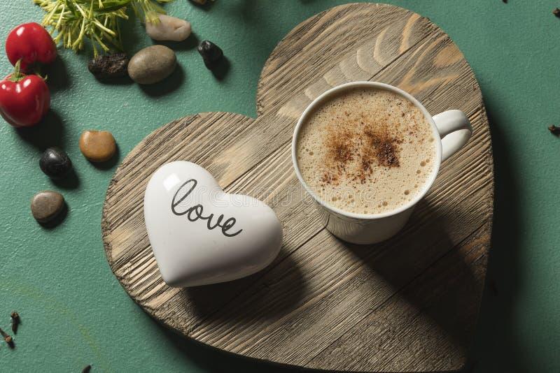 Heiße Schokoladen-Getränk auf Herzen formte hölzerne grüne Hintergrundwortliebe stockfotografie