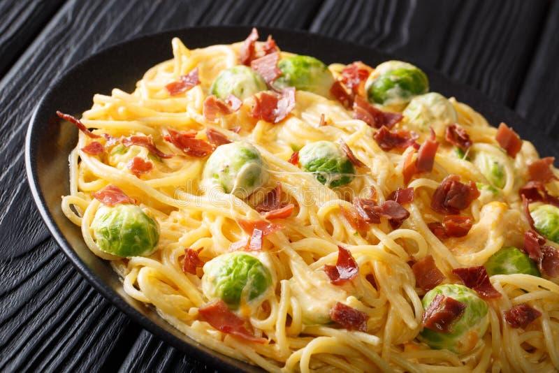 Heiße Spaghettis gekocht mit Rosenkohl, Speck, Knoblauch auf dem Tisch bedeckt mit sahniger Käsesoßennahaufnahme auf einer Platte lizenzfreie stockbilder