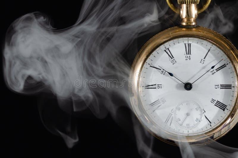 Heiße Zeit: Taschen-Uhr eingeschlagen im weißen Rauche stockbild