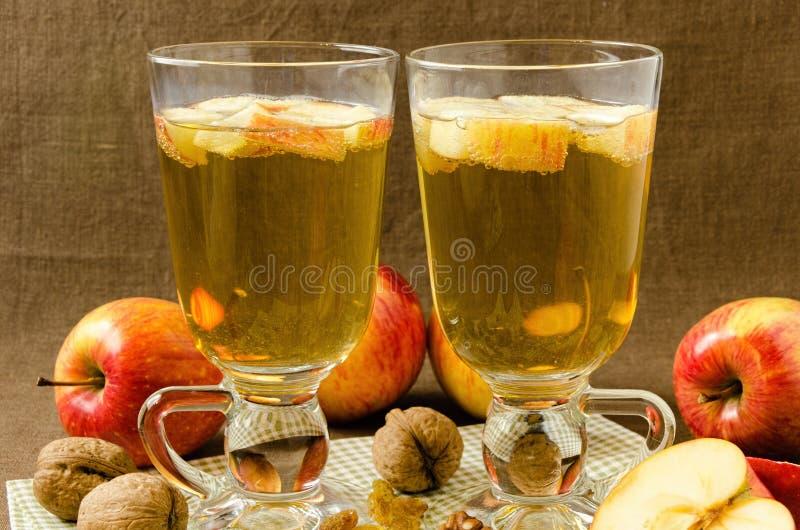 Heißer Apfelwein mit Äpfeln und Scheiben in den Schalen lizenzfreie stockfotografie